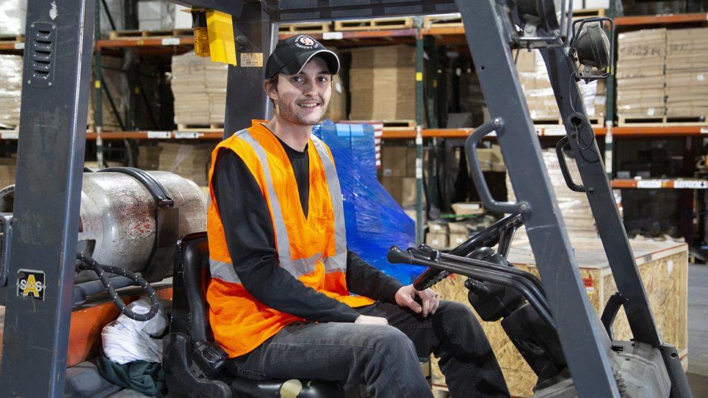 ein Junge, der an einem Gabelstapler arbeitet und auf die Kamera schaut.